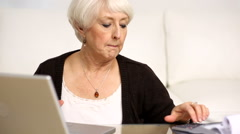 Senior woman working on personal finances - stock footage