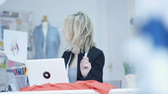 4K Portrait of smiling dressmaker working on laptop in her studio - stock footage