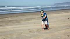 Young boy running on beach with towel Stock Footage