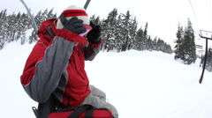 Snowboarder on lift looks at camera Stock Footage