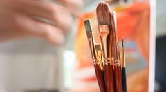 Artist picks up paintbrush Stock Footage