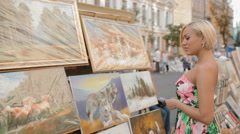 Young woman consider the paintings Stock Footage