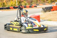 Little girls are driving Go- Kart car in a playground racing track - stock photo