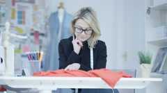 Stock Video Footage of 4K Dressmaker in her studio, looking at magazine for inspiration