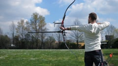 Stock Video Footage of Field Archery, young man shooting an arrow with his bow, focus on foreground