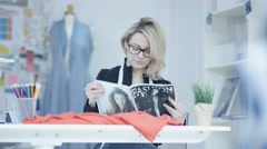 Stock Video Footage of 4K Smiling dressmaker in her studio, looking at magazine for inspiration