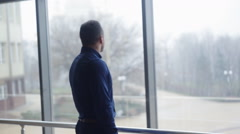 Stock Video Footage of A businessman looks out the window in a contemplative way. Medium shot