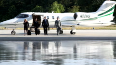 Businesspeople walking to corporate jet Stock Footage