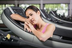 Woman leaning on treadmill - stock photo