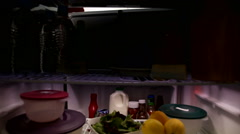 Man pigs out on cake in refrigerator Stock Footage