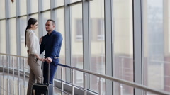 Portrait of young happy couple with baggage looking at one another in airport - stock footage