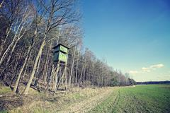 Vintage cross processed photo of hunting pulpit at the edge of a forest. Stock Photos