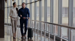 Happy loving couple in casual wear walking with a luggage by airport terminal. - stock footage