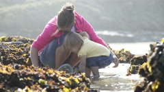 Mother and daughter looking in tide pools Stock Footage