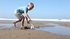 Boy playing with toy boat at beach Stock Footage