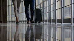 Happy loving couple in casual wear walking with a luggage by airport terminal. Stock Footage