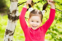 Beautiful girls face happily smiling. Child making funny faces Kuvituskuvat