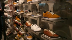Shelves with sports shoes in the hall of fashion store - shopping - stock footage