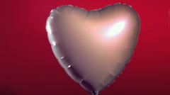 Valentine's Day balloon shot by arrow - stock footage