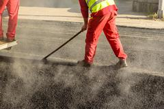 Construction worker leveling fresh asphalt pavement during road repair - stock photo