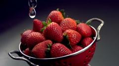 Rinsing strawberries in colander Stock Footage