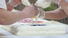 Cookery hands of culinary experts squeeze the cream on a big white cake - stock footage