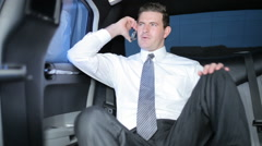 Businessman in limo talking on cell phone - stock footage