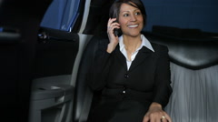 Businesswoman in limo talks on cell phone - stock footage