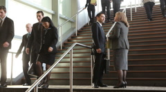 Businesspeople meet on steps of lobby Stock Footage