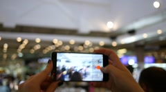Hands holding shooting video via smartphone of a festival event Stock Footage