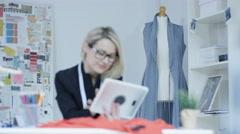 4K Portrait of smiling dressmaker looking at computer tablet in her studio - stock footage