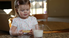Little girl having milk and cookies Stock Footage