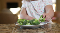 Young girl eating broccoli - stock footage