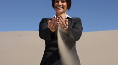 Businesswoman in desert with sand falling through hands Stock Footage