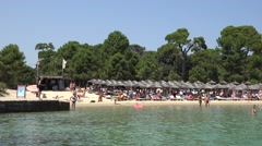 4K Pan right crowded Koukounaries beach people enjoy water sea Skiathos emblem  Stock Footage