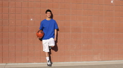 Teen standing by brick wall with basketball Stock Footage