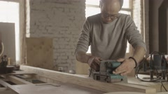 Aged woodworker careful treat wooden board by belt sander. Manufacturer Stock Footage