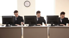 Three identical businessmen working at desks Stock Footage