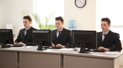 Three identical businessmen at computers Stock Footage