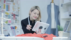 4K Portrait of smiling dressmaker looking at computer tablet in her studio - stock footage
