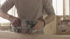 Aged woodworker careful process wooden board by belt sander. Manufacturer Stock Footage
