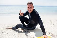 Happy surfer in wetsuit sitting with surfboard on the beach - stock photo