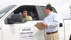 Driving instructor congratulates teen driver Stock Footage