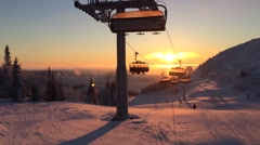Cableway in the rays of the setting sun among snow-capped mountains Stock Footage