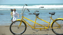 Couple at beach with tandem bicycle in foreground Stock Footage