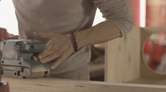 Aged woodworker careful process smooth of wooden board by belt sander Stock Footage