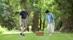 Mature couple walking in park with picnic basket Stock Footage