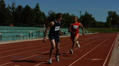 Athletes pass the baton in a track relay Stock Footage
