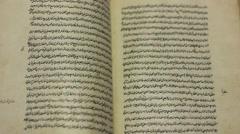 leafing through old handwritten book in Arabic - stock footage