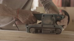 Carpenter careful process surface of wooden board by belt sander Stock Footage
